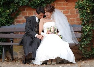 Brautpaar romantisch auf Parkbank